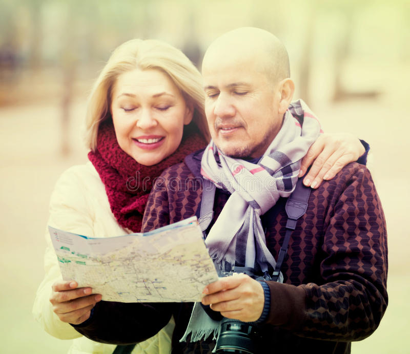 Senior couple of travellers with map stock images