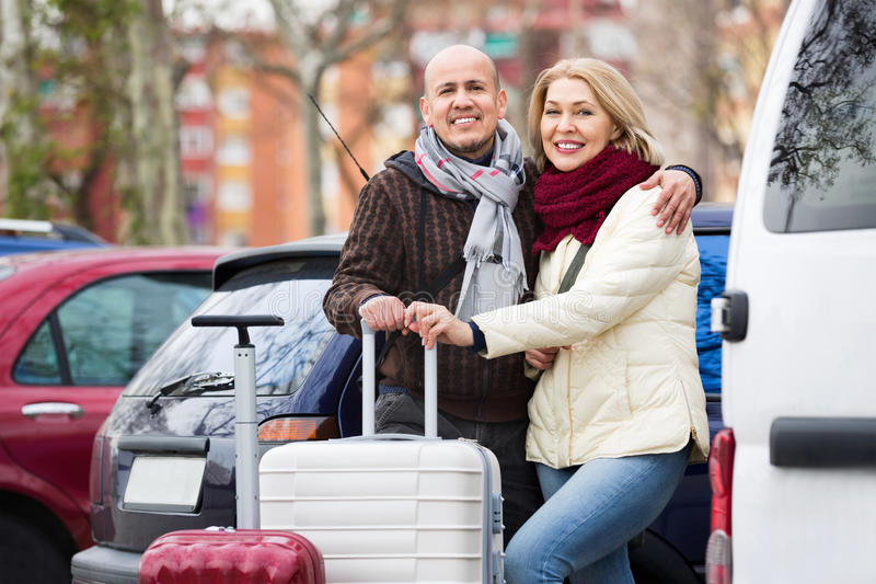 Senior couple of travellers posing with trollers. Near parked car royalty free stock photos