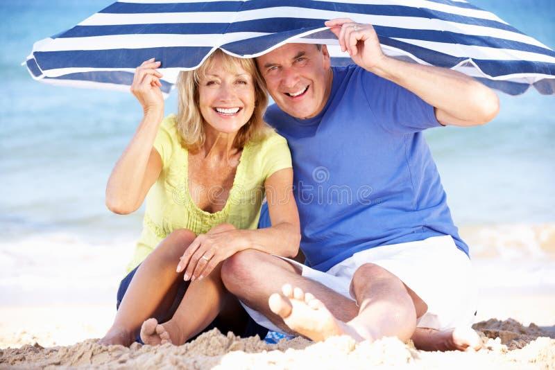 Senior Couple Under Beach Umbrella royalty free stock photo