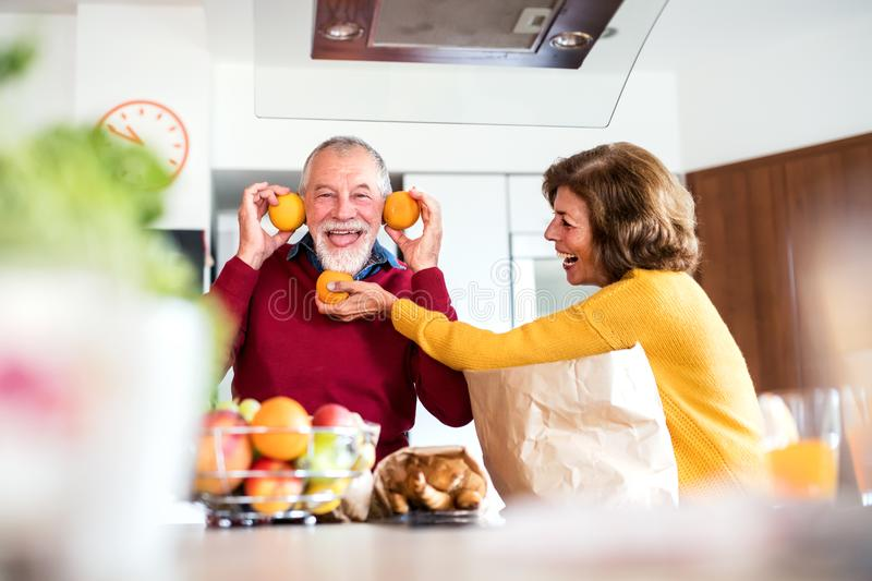 Senior couple unpacking food in the kitchen, having fun. Senior couple unpacking food in the kitchen. An old men and women inside the house, having fun royalty free stock photos