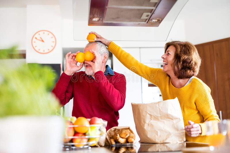 Senior couple unpacking food in the kitchen, having fun. Senior couple unpacking food in the kitchen. An old men and women inside the house, having fun royalty free stock image