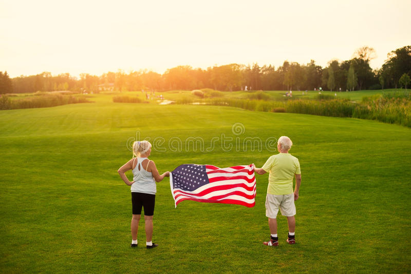 Senior couple with US flag. Back view of elderly people. Be example for others. Patriots are always in shape stock image