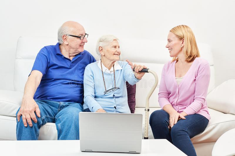 Senior couple using laptop computer at retirement home. Senior couple with laptop computer and a young women in retirement home stock photo