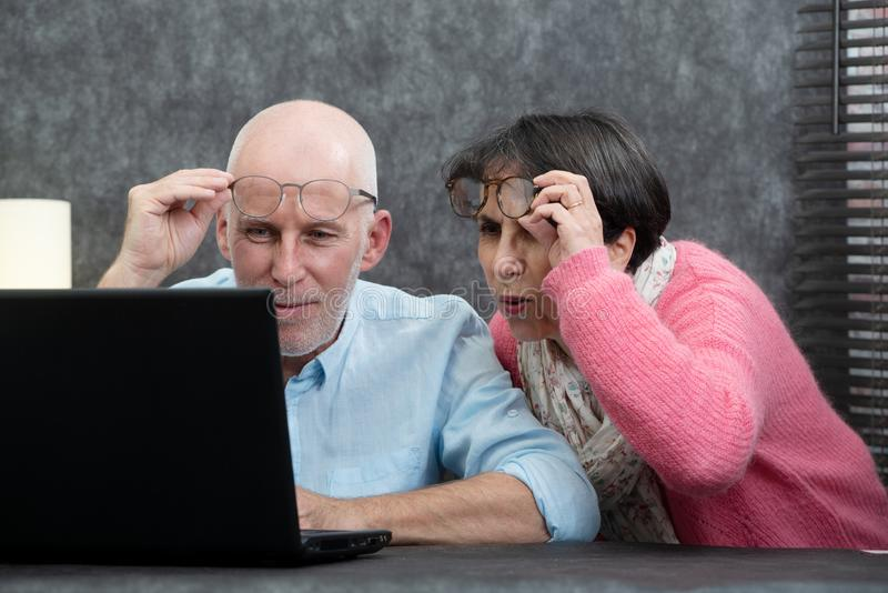 Senior couple using laptop, they having difficulties and vision problems. A senior couple using laptop, they having difficulties and vision problems royalty free stock images