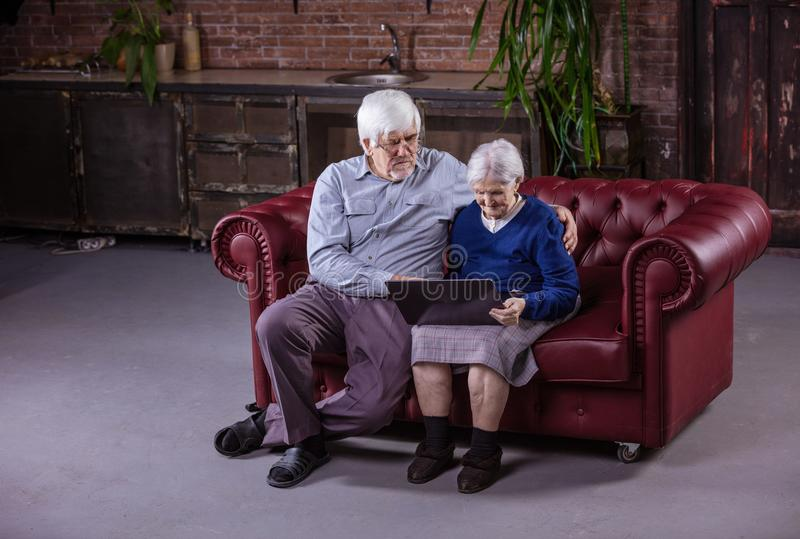 Senior couple using laptop while sitting on couch stock photos