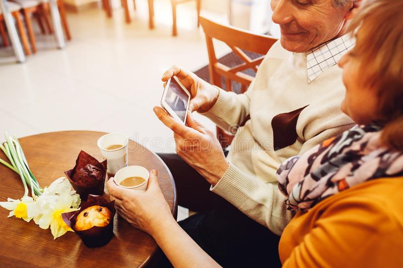 Senior couple using a phone in cafe. Retired people learn how to use new technolodies. Family relaxes in cafe royalty free stock photos