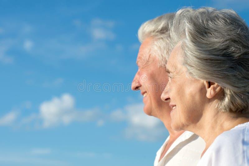 Senior couple on vacation. Amusing senior couple on vacation against the sky stock photo