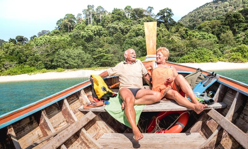 Senior couple vacationer relaxing at island hopping tour after beach exploration during snorkel boat trip in Thailand - Active. Elderly and travel concept on stock photography
