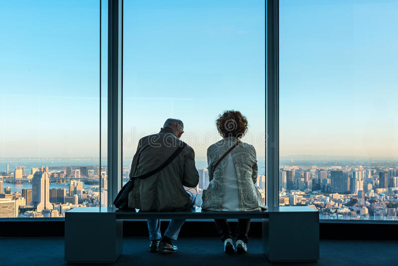 Senior couple wait for the sunset in Tokyo. Tokyo, Japan - October 13, 2015: A senior couple waits for the sunset sitting on a bench on top od one of the highest stock photos