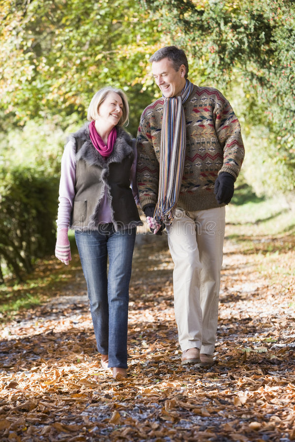 Senior couple walking along autumn path royalty free stock photo
