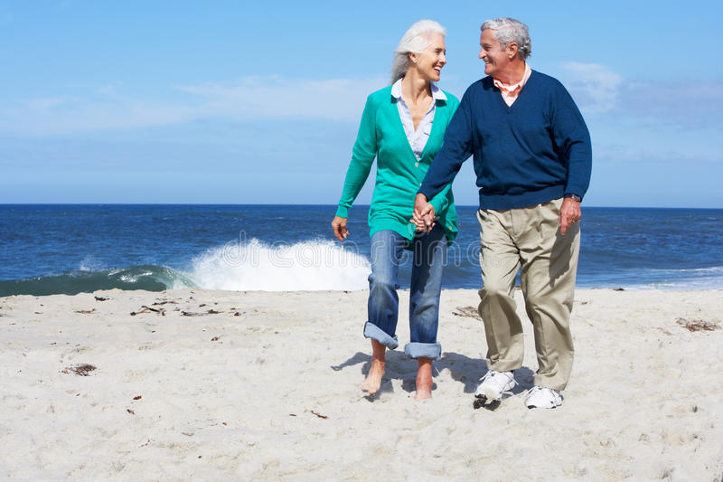 Senior Couple Walking Along Beach Together. Smiling at each other royalty free stock image
