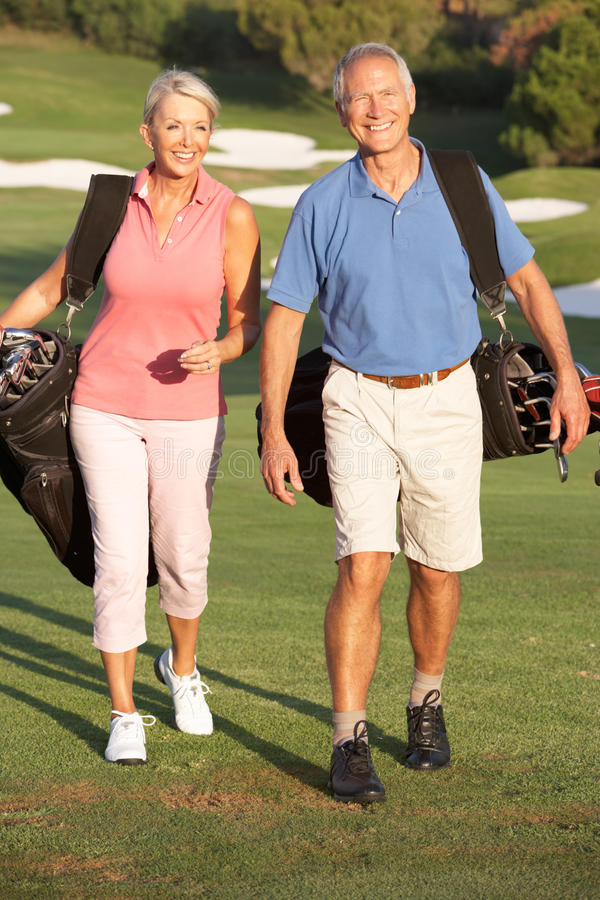 Senior Couple Walking Along Golf Course royalty free stock photography
