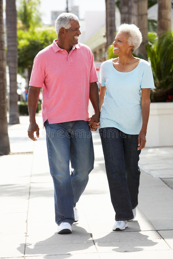 Download Senior Couple Walking Along Street Together Stock Photo - Image: 27959796
