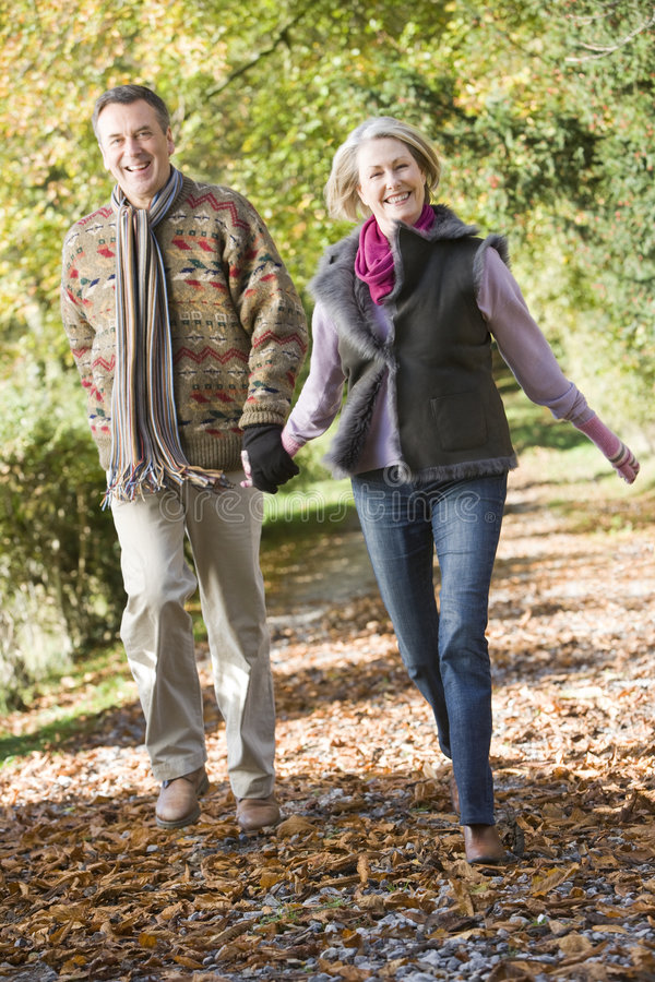 Senior couple walking through autumn woods royalty free stock photography