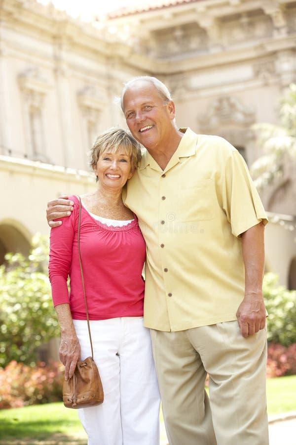 Senior Couple Walking Through City Street stock images