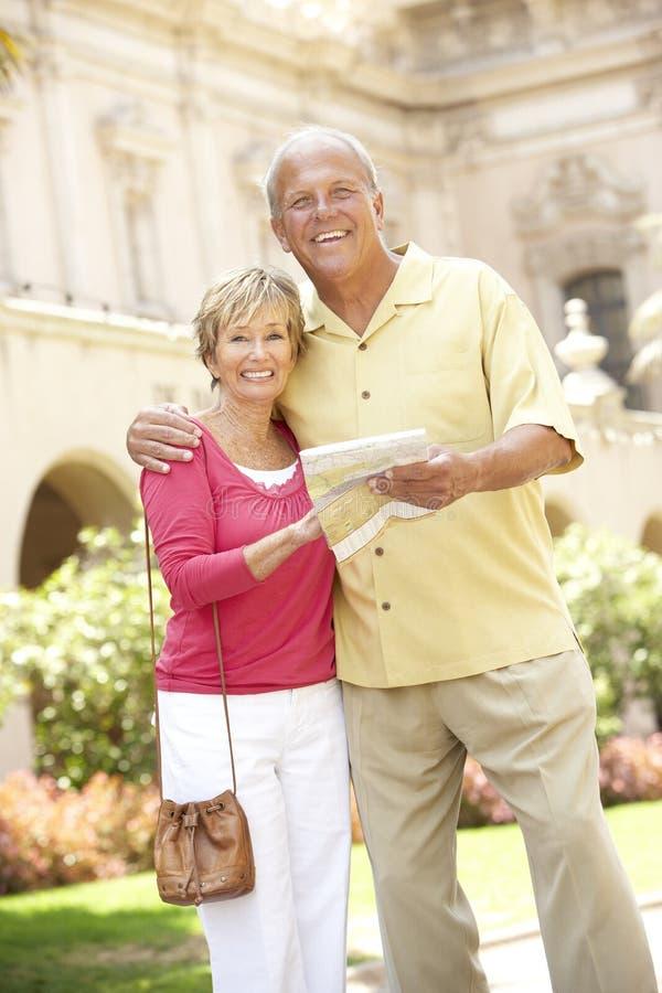 Senior Couple Walking Through City Street With Map royalty free stock image