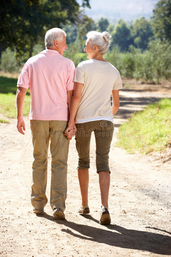 Senior couple walking in country. Senior couple on country walk holding hands walking away from camera royalty free stock photos