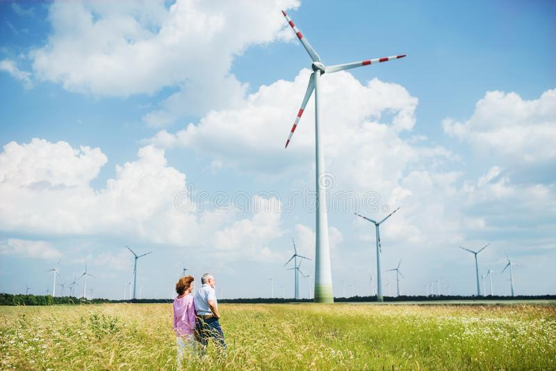 Senior couple walking on field on wind farm. Copy space. A senior couple walking on field on wind farm. Copy space stock photos