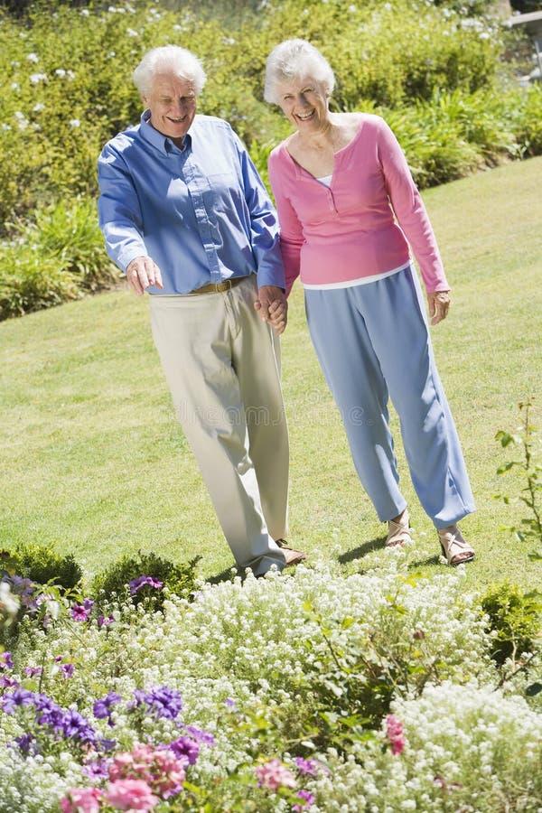 Senior couple walking in garden royalty free stock photo