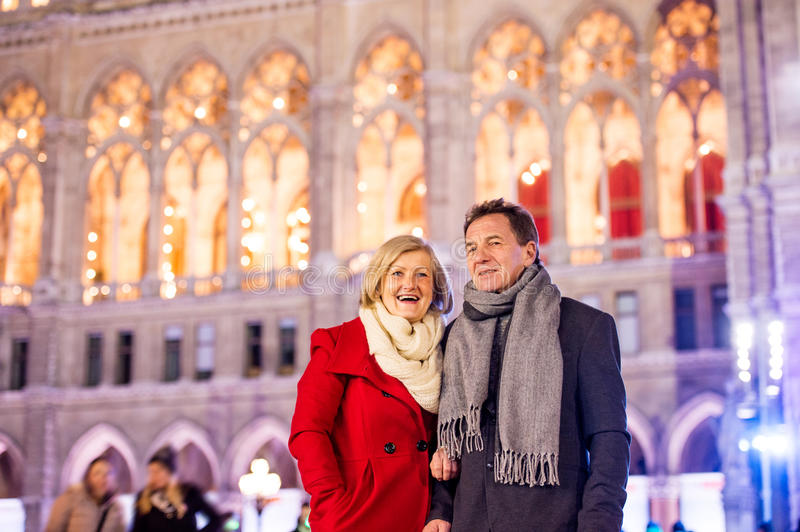 Senior couple walking in night city. Winter, Historical building royalty free stock images