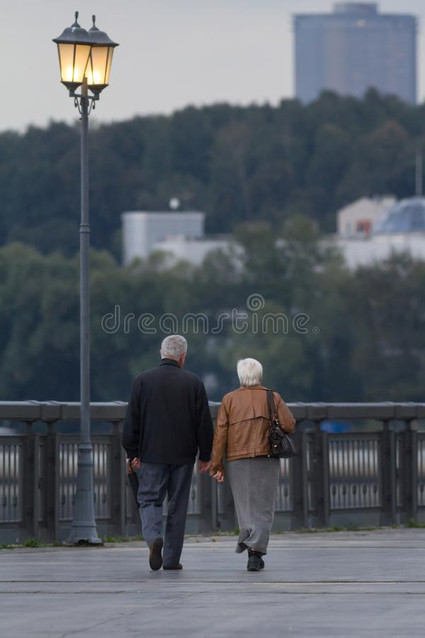 Senior couple walking in park at evening royalty free stock photo