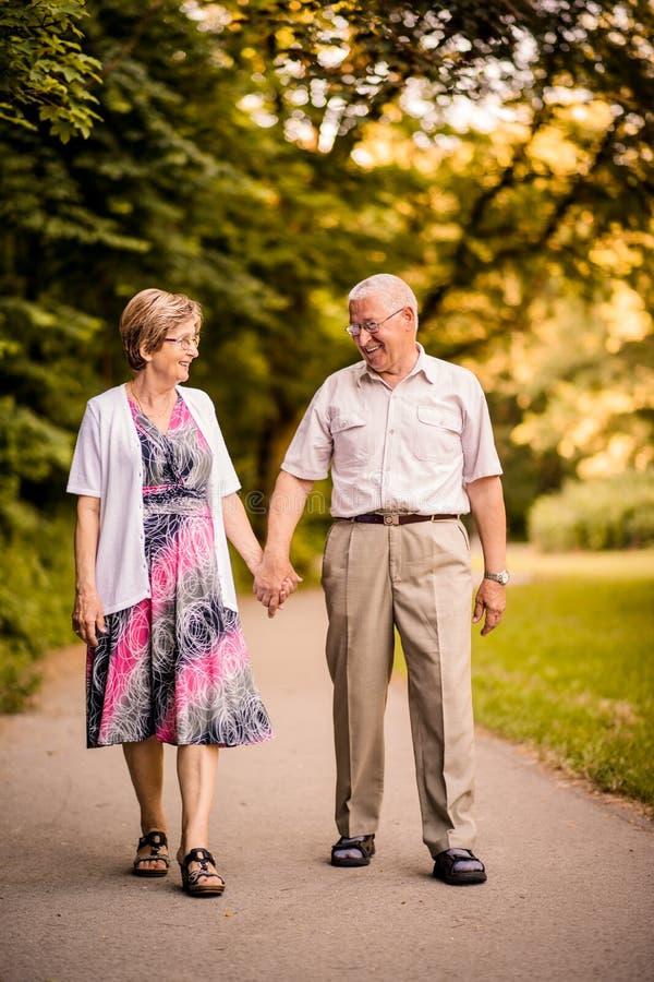 Senior couple walking in park stock images