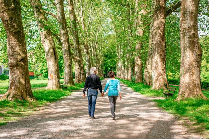 Senior Couple Walking Through A Park stock photo