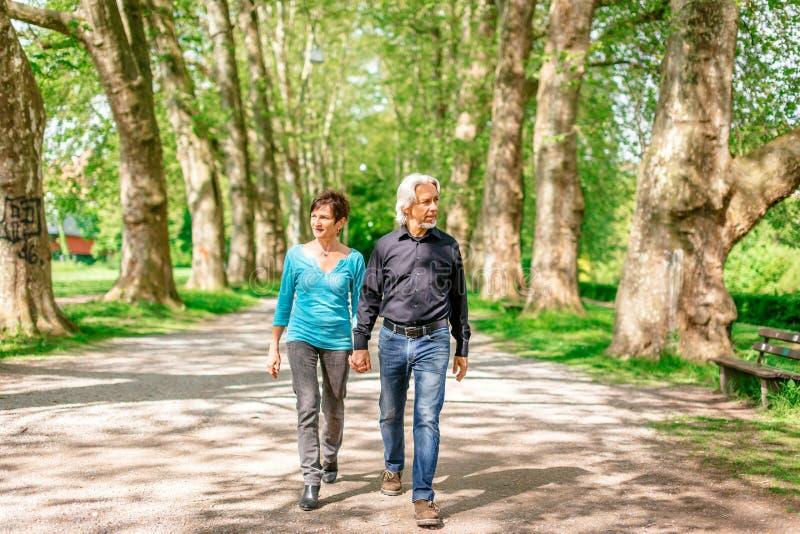 Senior Couple Walking Through A Park stock photography