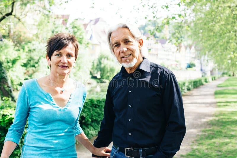 Senior Couple Walking Through A Park royalty free stock photos