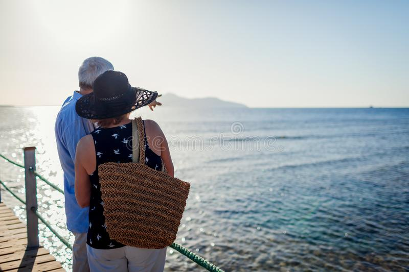 Senior couple walking on pier by Red sea. People enjoying summer vacation and landscape. royalty free stock photos