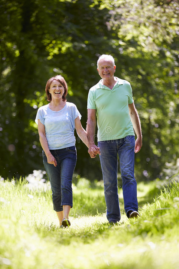 Download Senior Couple Walking In Summer Countryside Stock Photo - Image: 54981666