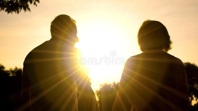 Senior couple watching sunset together, romantic date, paradise with beloved stock photos