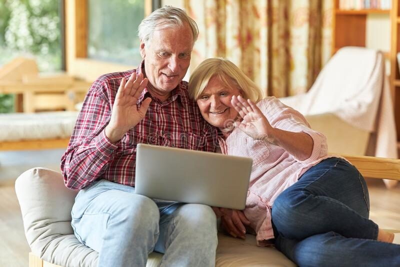 Senior couple watching video chat on laptop computer. Smiling senior couple watching video chat on laptop computer in living room stock photos