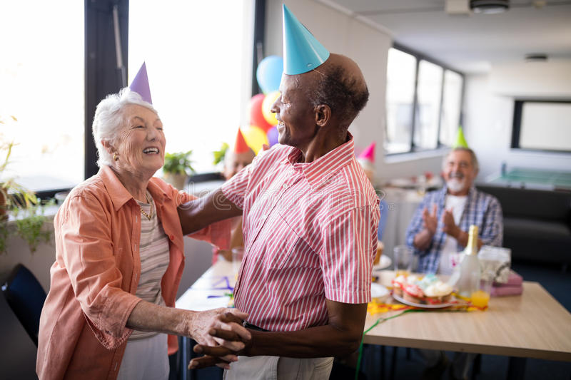 Senior couple wearing party hats dancing at birthday party royalty free stock photo