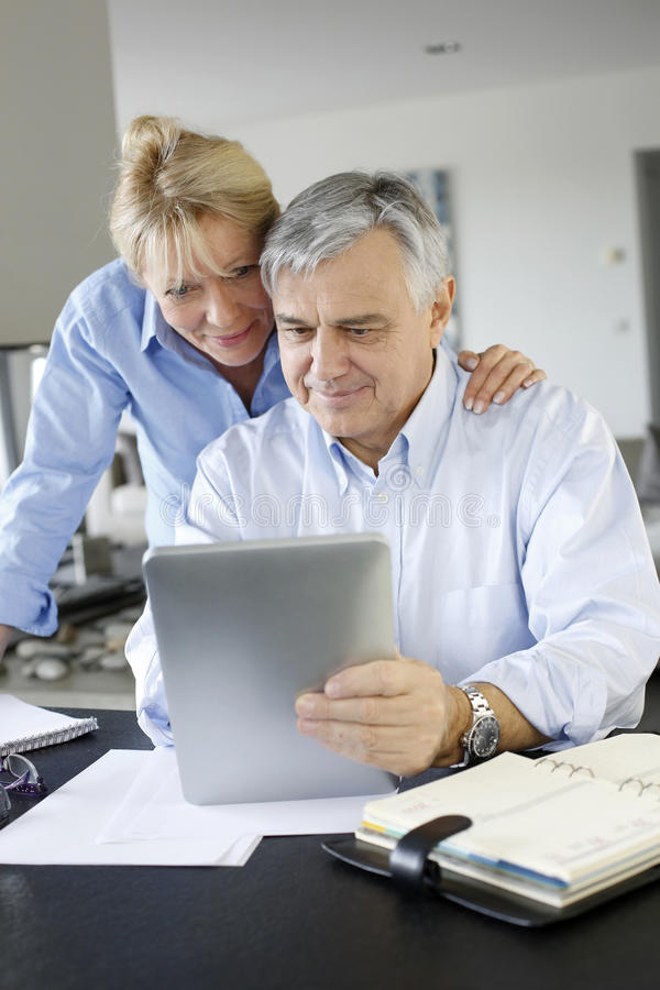 Senior couple websurfing on tablet. Senior couple looking at bank account on digital tablet stock photo