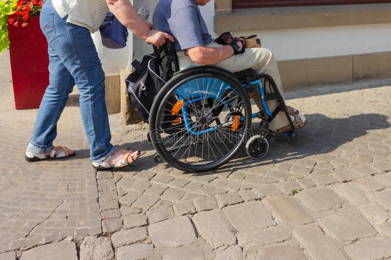 Senior couple with wheel chair. At sunny springtime day in south germany royalty free stock photography