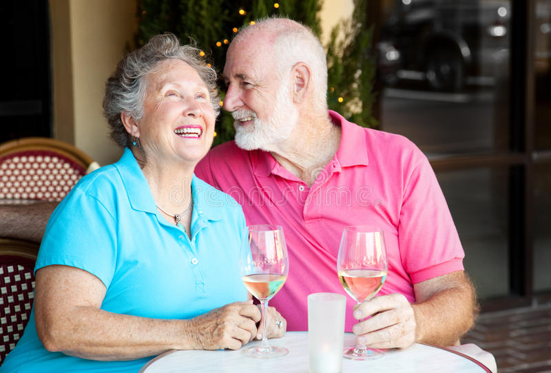 Senior Couple - Wine and Conversation. Senior couple at a cafe, enjoying wine and conversation together stock photography