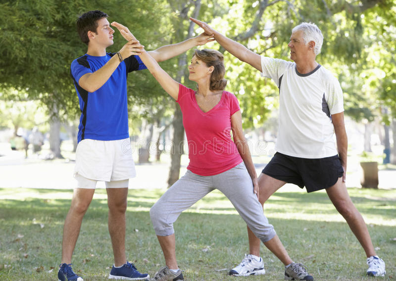 Senior Couple Working With Personal Trainer In Park stock photos