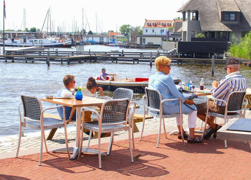 Elderly couple young people cafe terrace drinks lake, Loosdrecht, Netherlands. Seniors couple and young people are eating and drinking at an outdoor cafe stock image