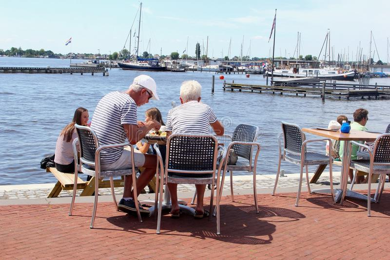 Senior couple young people terrace lake, Loosdrecht, Netherlands. Seniors couples and young people are eating and drinking at an outdoor cafe restaurant terrace stock images