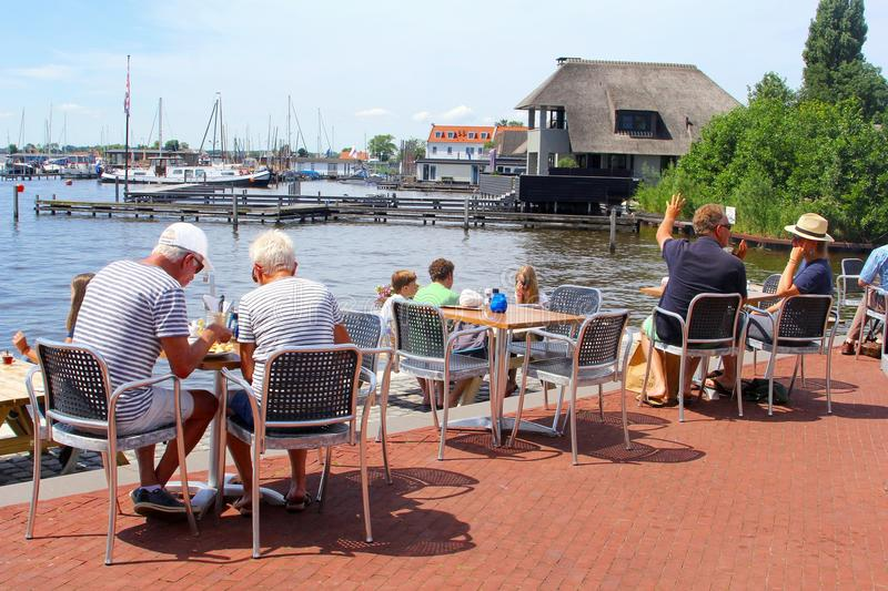 Senior couples families lake cafe terrace, Loosdrecht, Netherlands. Seniors couples and family with young children are eating and drinking at an outdoor cafe royalty free stock photography