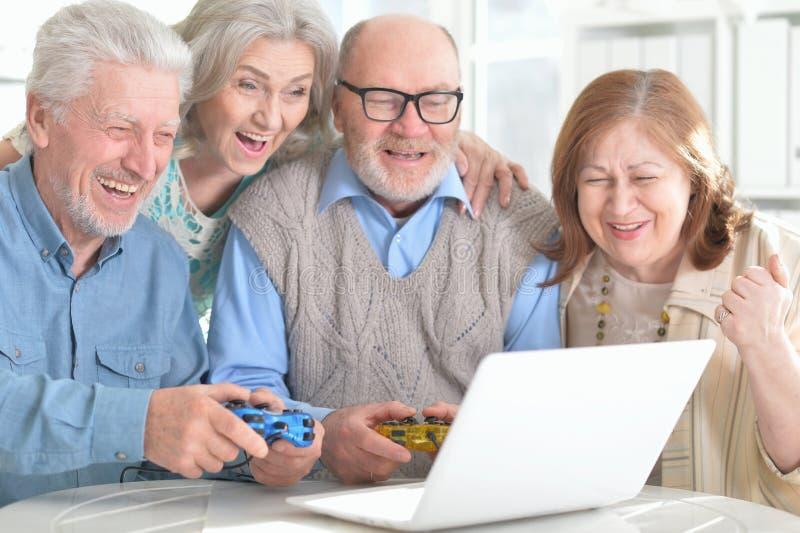 Senior couples reading newspaper stock photo