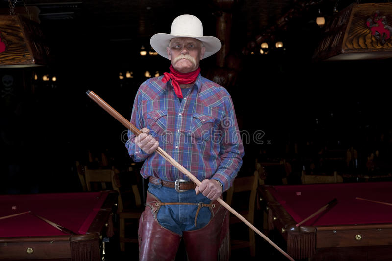 Senior Cowboy Standing in a Pool Hall. Portrait of a senior man in western wear, holding a pool cue and standing in a pool hall. He is looking at the camera with stock photos