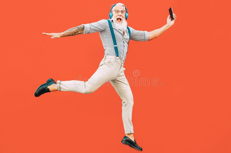 Senior crazy man jumping while listening music outdoor - Hipster male having fun dancing and celebrating life outside. Happiness, technology and elderly royalty free stock photo