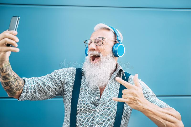 Senior crazy man taking self video while listening music with headphones - Hipster guy having fun using mobile smartphone. Playlist apps - Happiness, technology stock images