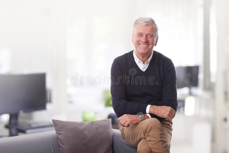 Senior creative director. Portrait of confident senior director sitting at his office while looking at camera and smiling stock photo