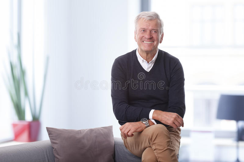 Senior creative director. Portrait of confident senior director sitting at his office while looking at camera and smiling royalty free stock photography