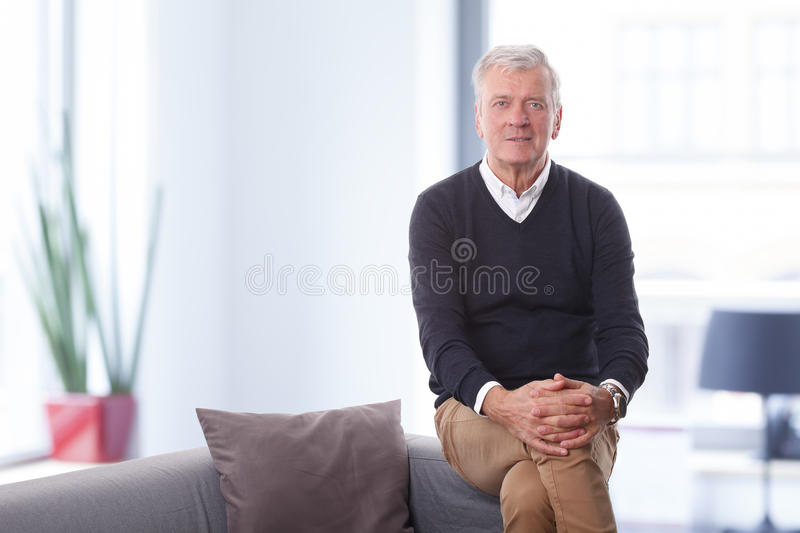 Senior creative director. Portrait of retired creative director sitting at his office while looking at camera and smiling royalty free stock images
