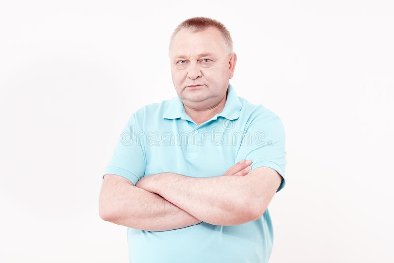 Senior with crossed arms. Portrait of serious aged man wearing blue shirt standing with crossed arms against white wall - retirement concept stock images