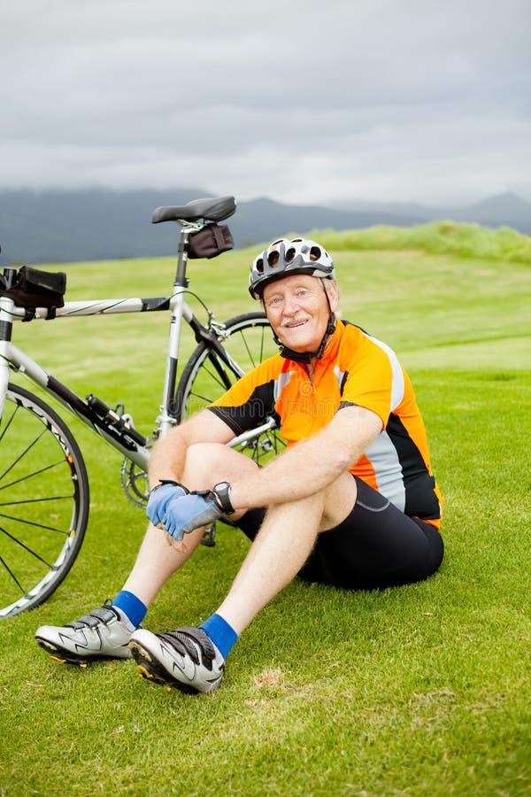 Senior cyclist resting. Happy senior cyclist resting on grass royalty free stock photography